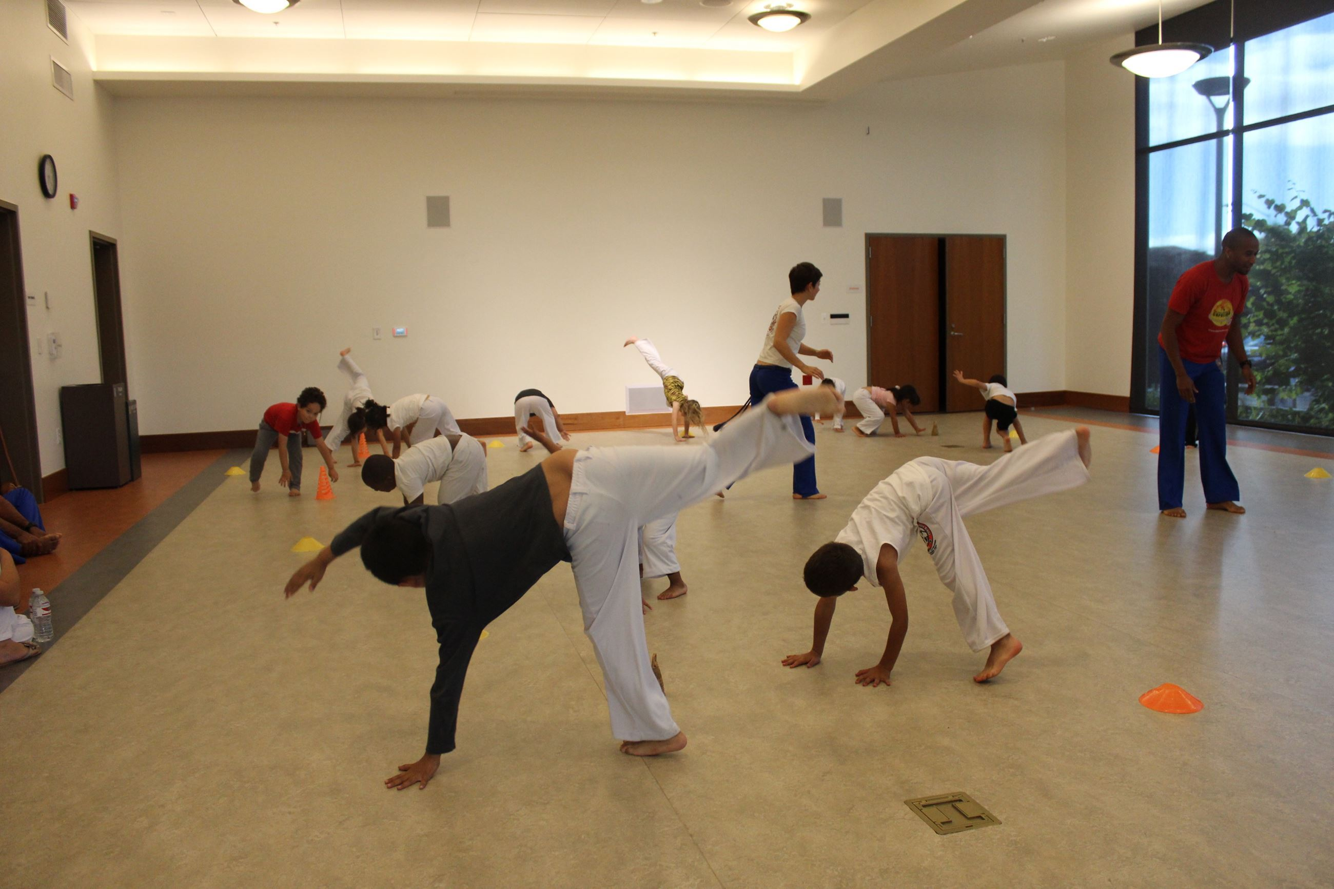 Capoeira participants kicking